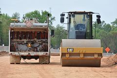 Roller machine gets refueled by fluids truck stock photography