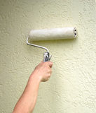 Roller paint on the wall. Roller with paint on the wall Stock Photo