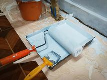 Roller painted walls. Clean paint roller on top of blue paint can for home diy decorating Royalty Free Stock Images
