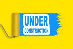 Roller painter blue stroke on yellow background with words under construction Stock Photography
