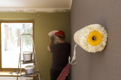 Roller for painting against grey wall. Decorator choosing color for walls on background Stock Photos