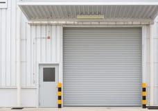 Shutter door factory. Roller shutter door and concrete floor outside factory building for industry background Stock Images