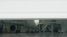 Roller shutter door and plane in hangar background. Business jet airplane is in hangar. Private corporate jet parked in