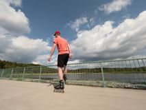 Roller skater in action. Man ride in inline skates ride along promenade handrail, sky in background Stock Photos