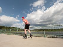 Roller skater in action. Man ride in inline skates ride along promenade handrail, sky in background Royalty Free Stock Photography