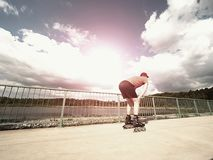Roller skater in action. Man ride in inline skates ride along promenade handrail, sky in background Stock Images