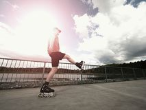 Roller skater in action. Man ride in inline skates ride along promenade handrail, sky in background Stock Photography