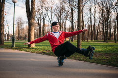Roller skater doing balance exercise on sidewalk. In city park. Male rollerskater leisure Royalty Free Stock Photography