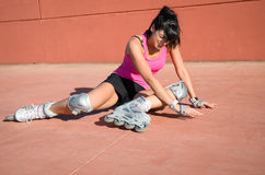 Roller skater fall. Female roller skater accident over hard asphalt. She wears protections and sport wear and shows face of suffering Stock Images
