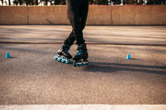 Roller skater legs in skates, balance exercise. On sidewalk in city park. Male rollerskater leisure Royalty Free Stock Images