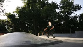 Roller skater ride in park. Boy legs in in-line hard shell boots blades. Doing tricks. Young man spending his leisure. Time in the skate park stock footage