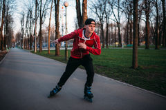 Roller skater rides by sidewalk in city park. Male rollerskater leisure Stock Image