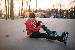 Roller skater sitting on asphalt in city park. Young roller skater sitting on asphalt in city park. Male rollerskater, extreme sport Royalty Free Stock Images