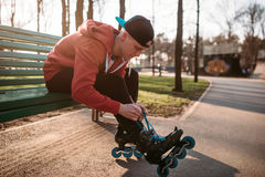 Roller skater sitting on bench and lace up skates. Roller skater sitting on the bench and lace up skates. Male rollerskater leisure in city park Royalty Free Stock Image