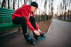 Roller skater sitting on bench and lace up skates. Roller skater sitting on the bench and lace up skates. Male rollerskater leisure in city park Stock Photography