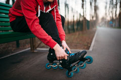 Roller skater sitting on bench and lace up skates. Roller skater sitting on the bench and lace up skates. Male rollerskater leisure in city park Stock Images