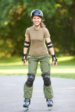 Roller skates. Young smiling woman in park. Roller skates Royalty Free Stock Photo