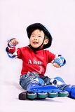 Roller skating boy sitting on ground. A picture of a little chinese boy sitting on the ground and laughing happily Stock Photo