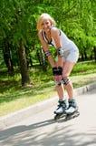 Roller-skating de fille en stationnement Image libre de droits