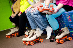 Roller Skating feet. A row of Roller Skaters prepare for skating by putting their feet into skates Royalty Free Stock Image