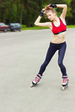 Roller skating girl in park rollerblading on inline skates. Mixed race Asian Chinese / Caucasian woman in outdoor activities Royalty Free Stock Photo