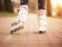 Roller skating in the park. Close up of little girl roller skating in the park Stock Photography