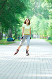 Roller skating sporty girl in park rollerblading on inline skate Royalty Free Stock Photos