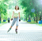 Roller skating sporty girl in park rollerblading on inline skate Stock Photo