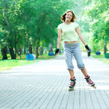 Roller skating sporty girl in park rollerblading on inline skate Stock Photography
