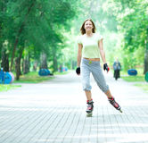 Roller skating sporty girl in park rollerblading on inline skate Royalty Free Stock Images