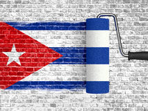 Roller to paint on white brick wall with cuba flag, wall with dripping paint,real texture color red blue and white of cuban flag Royalty Free Stock Photo