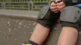 Rollerblade equipment kneecap wrist pad protection. Rollerblade hobby equipment. Knee caps and wrist pads protection. Athletic boy resting on a ramp stock footage