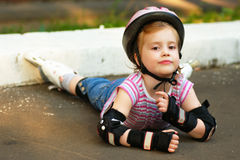 Rollerblade girl. The little girl has fallen on the ground while rollerblading Stock Images