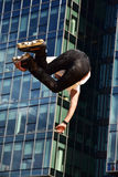 Rollerblade jump trick at a city background. Stock Image