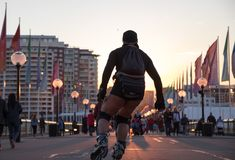 Rollerblader skating into the sunset. Rollerblade silhouetted against an orange sunset in a busy pedestrian mall Royalty Free Stock Photos