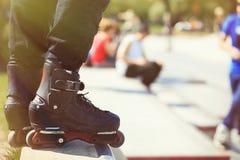 Rollerblader intégré agressif se tenant sur la rampe dans le skatepark Photo stock