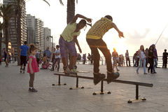 Rollerbladers performing tricks, Beirut. Rollerbladers performing tricks while a little girl watches them. Beirut Royalty Free Stock Image