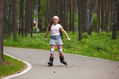 Rollerblades del montar a caballo de la muchacha Fotografía de archivo libre de regalías