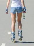 Rollerblades del paseo de la mujer en el parque. Visión trasera. Fotos de archivo libres de regalías