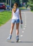 Rollerblades di giro della donna nel parco. Vista posteriore. Fotografie Stock