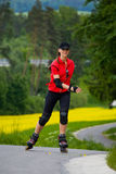 Rollerblades for girls. A young woman ride rollerblades in the park Royalty Free Stock Image