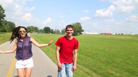 rollerblading在一个美妙的晴天的愉快的年轻夫妇在公园,跳舞 股票录像