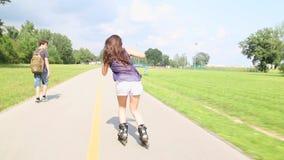 rollerblading在公园的年轻可爱的妇女在一个美好的晴天 影视素材