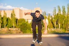rollerblading在城市公园的愉快的年轻人在日落 免版税库存照片