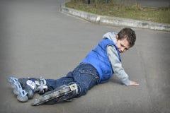 rollerblading春天的男孩和在路跌倒了 免版税库存图片