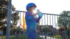 Rollerblading-Kind trinkt reines Wasser von der Flasche auf Freilicht in der Hintergrundbeleuchtung stock video footage