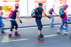 Rollerblading people on a city street Stock Photos