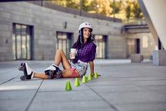 Rollerblading sammanträde för lycklig tonåring på gata- och drinkkaffe royaltyfri fotografi