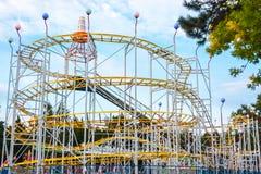 Rollercoaster i aftonen mot blå himmel Arkivfoton