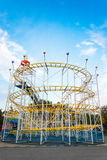 Rollercoaster i aftonen mot blå himmel Royaltyfria Bilder